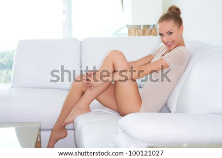 Sideview of beautiful introspective woman in skimpy outfit sitting on a white sofa with her bare feet up on the coffee table - stock photo