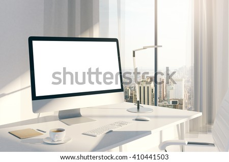 Sideview of creative desktop with blank white computer screen in sunlit office with windows and city view. Mock up, 3D Rendering - stock photo