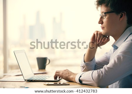Sideview of thinking caucasian businessman sitting at office desk with smartphone and coffee cup, using notebook. Blurry city background - stock photo