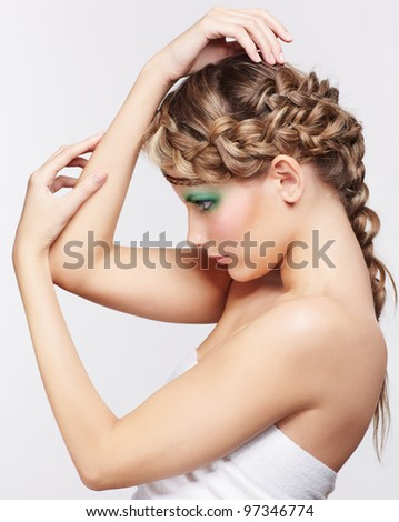 sideview portrait of beautiful young dark blonde woman with creative braid hairdo posing on gray - stock photo