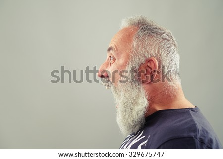 sideview portrait of screaming senior man with grey-haired beard  - stock photo
