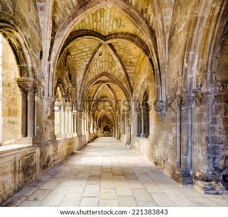 sideway of the 14th century cloister attached to the se cathedral of Lisbon, capital of Portugal, with weathered stone pillars - stock photo