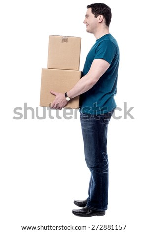Sideways of casual man carrying stack of boxes - stock photo