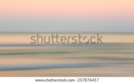 Sideways panning across the ocean reflecting the soft light of sunrise in Hawaii - stock photo