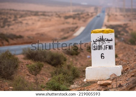 Sidi Ifini 6 kilometres - road sign distance indicator on the road to Sidi Ifini with the road in the background, Morocco - stock photo