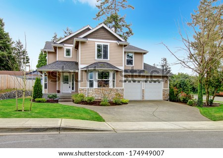 Siding house with tile roof, enclosed garage, and beautiful curb appeal - stock photo