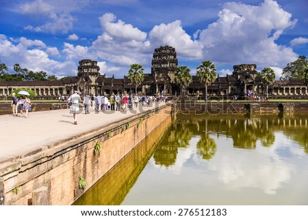 SIEM REAP, CAMBODIA - DECEMBER 5: Crowd of people at the main entrance of Angkor Wat on December 5, 2014. It is a temple complex in Cambodia and the largest religious monument in the world. - stock photo