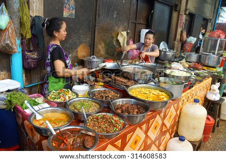 SIEM REAP, CAMBODIA - FEB 16, 2015 - Woman cooking lunch in the market of  Siem Reap,  Cambodia - stock photo