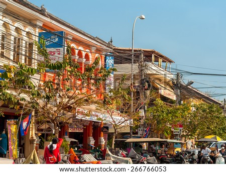 SIEM REAP, CAMBODIA - FEBRUARY 18, 2014: Motorbikes, tuk tuks, tourist shops, and electrical lines clog a street in this gateway city to the world heritage site of Angkor Wat. - stock photo