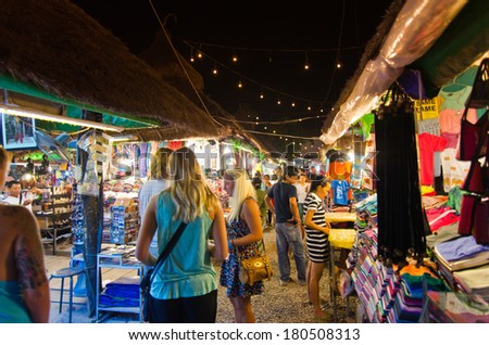 SIEM REAP, CAMBODIA - JAN  4, 2014: Unidentified tourists shop at the night market of Siem Reap on Jan 4,2014. It serves as a gateway to the world famous Angkor temples and is a major tourist hub. - stock photo