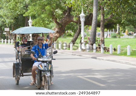 SIEM REAP, CAMBODIA - JUNE 28, 2014: An unidentified tuktuk driver drives Caucasian tourists in the street. The town is famous for its proximity to Angkor temples and night markets. - stock photo