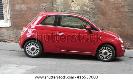 SIENA, ITALY, - CIRCA APRIL 2016: red FIAT 500 car (new version) parked on a street in the city centre - stock photo