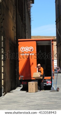SIENA, ITALY - CIRCA APRIL 2016: TNT post van parked in A Street Of The City Centre, With Postman Downloading Parcels - stock photo
