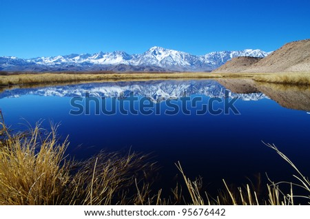 Sierra Mountain reflection in an oxbow of the Owens River with foreground grasses - stock photo