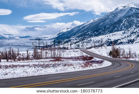Sierra Nevada Highway in Winter:  A scenic California highway curves among snowy mountains and a frozen lake near Yosemite National Park.  - stock photo