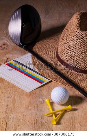 Siesta - straw hat and golf driver on a wooden table - stock photo