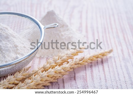 sieve white natural flour and ears of wheat on vintage wooden desk food and drink concept  - stock photo