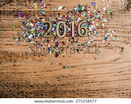 Sigh symbol from number 2016 in confetti, streamers on old retro vintage style wooden texture background Empty copy space for inscription Idea merry new year holiday year of monkey - stock photo