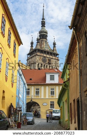 SIGHISOARA, ROMANIA - JULY 26, 2014: Clock tower and colorful houses in medieval citadel of Sighisoara, listed by UNESCO as World Heritage Site. Vlad Tepes (Dracula) was born here in 1431. - stock photo