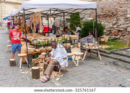 Sighisoara, Romania-July 03, 2015: The stall with wooden handicraft. A man produces them on the spot - stock photo