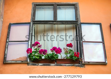 Sighisoara, Romania - June 23, 2013: Pink facade with windows and flowers from Sighisoara city old center, Transylvania, Romania - stock photo