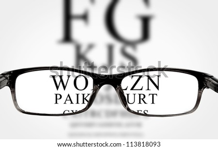 Sight test seen through eye glasses, white background isolated - stock photo