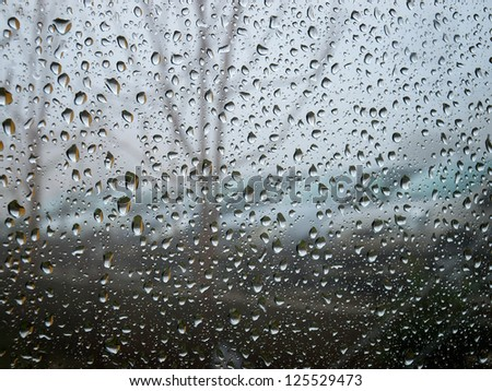 Sight to the moody and  rainy day through raindrops on a window - stock photo