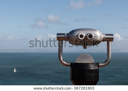 Sightseeing binoculars overlooking ocean with a sailboat in the distance. - stock photo
