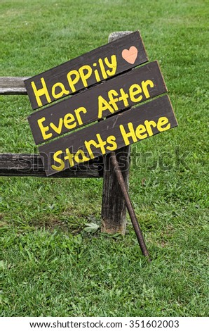 Sign Against Fence for Directions to a Happy Wedding - stock photo