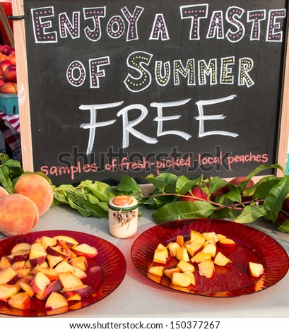 Sign at farm market for fresh peaches along with sign for free samples. - stock photo