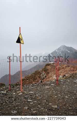 sign danger of falling from a height on top of the mountain rose peak 2320 m in Rosa Khutor, Sochi - stock photo