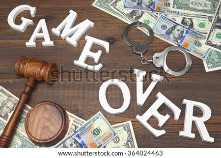 Sign Game Over, Money, Real Handcuffs, Judges Gavel On The Wood Rough Table Background. Concept For  Bankruptcy, Gambling, Fraud, Bribe, Bail, Illegal Income, Tax. Overhead View - stock photo