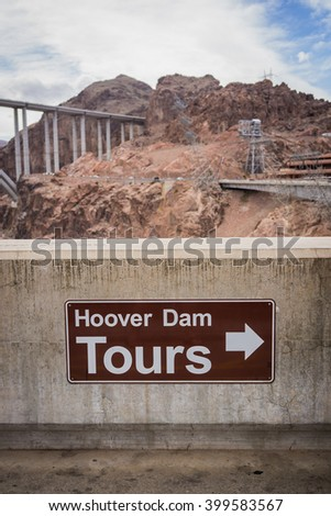 Sign guides people to the location of Hoover Dam tours at the dam site in the southwest of the United States. - stock photo