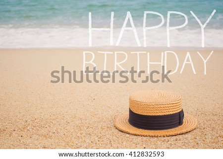 """Sign """"Happy Birthday"""" on the sandy beach by the ocean - stock photo"""