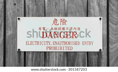 Sign of danger in the english language and chinese language on wood background - stock photo