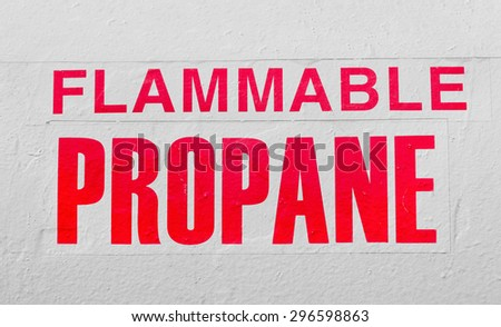 Sign of flammable propane is on a white metal container. Sign is a slight fade due to weathering.  - stock photo