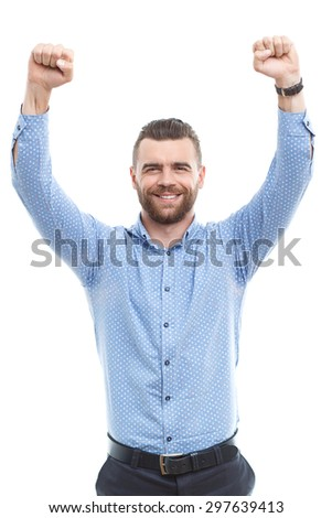 Sign of success. Youthful handsome man with beard raising his fists in air against isolated background  - stock photo