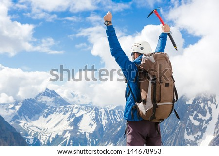 Sign of victory: climber on the top of the mountain - stock photo