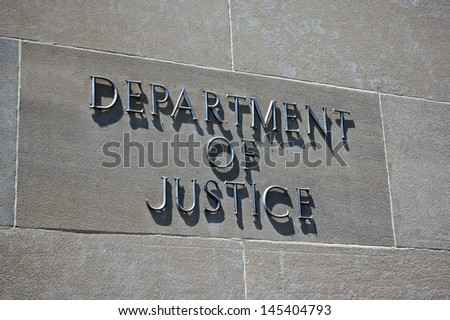 Sign on the exterior identifies the Department of Justice. - stock photo