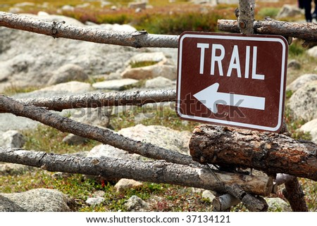 sign pointing to hiking trail - stock photo