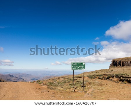 Sign post at summit with view of valley and winding road over mountains from South Africa to Lesotho over Sani Pass - stock photo