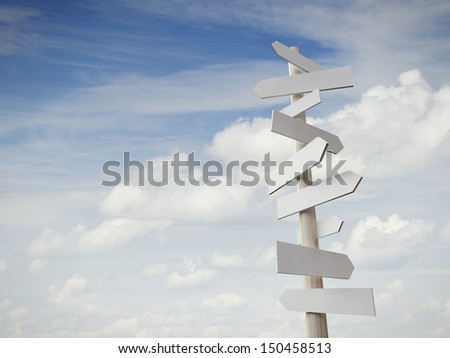 sign post with many arrows pointing on sky - stock photo
