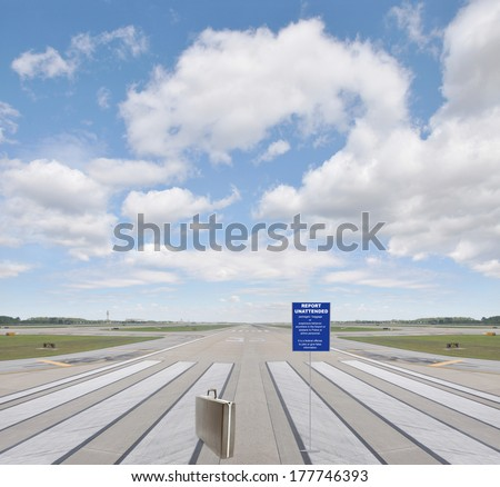Sign Report Unattended Baggage / Packages or suspicious behavior anywhere in the airport or plane to police or airline personnel. It's a federal offense to joke or give false info. Briefcase Runway - stock photo