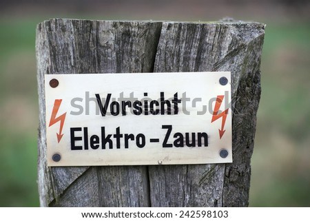 Sign saying: Caution, electric fence. - stock photo