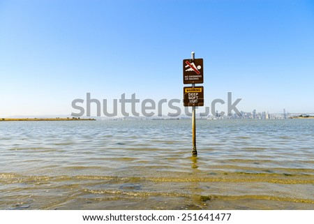 Sign warns of deep soft mud and against swimming - stock photo