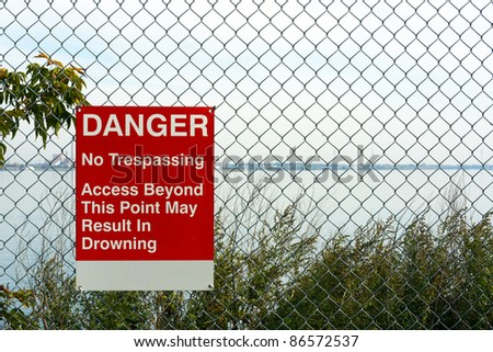 Sign warns of drowning in what appears to be calm waters - stock photo