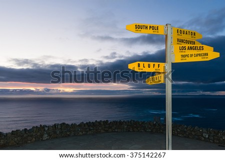 Sign with distances in km and nm from Cape Reinga, New Zealand at dusk - stock photo