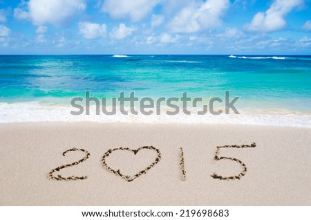 """Sign """"2015"""" with heart on the sandy beach by ocean - stock photo"""