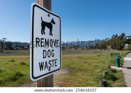 Sign with Remove Dog Waste next to a green park area - stock photo