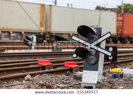 Signaling device at the railroad tracks and the train with containers. - stock photo
